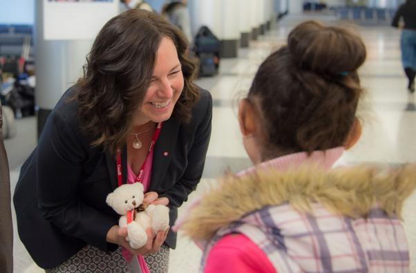 Kanada'nın Lübnan Büyükelçisi Michelle Cameron sığınmacıların Kanada'ya uçuşundan önce bir çocuğa oyuncak ayı verirken.
