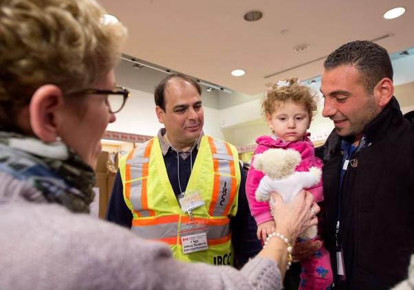 Ontario Başbakanı Kathleen Wynne yeni gelen sığınmacı ailenin çocuğuna bir oyunca ayı sunarken.
